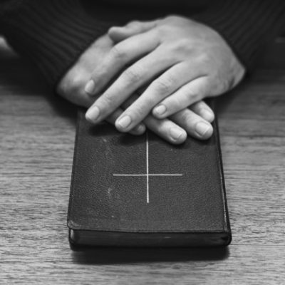Hands over bible on wooden table
